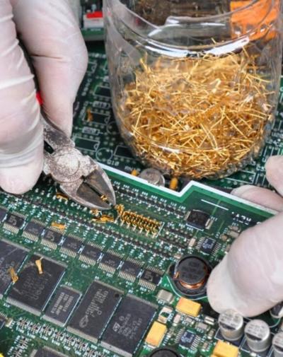 un opérateur récupère le métal de circuits imprimés à recycler